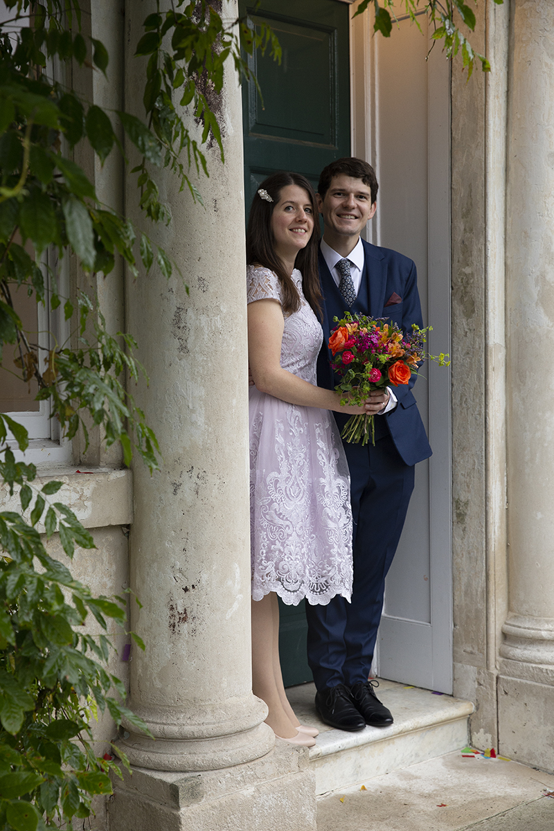Bridal couple outside green door. Kirsten Duberly Photography. Morden Park House wedding photography