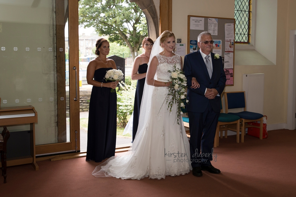 Bride and father entering church. Reigate wedding